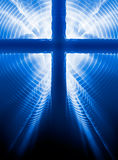Easter Cross. Easter crucifix silhouette on blue background with light rays from the back Royalty Free Stock Photo