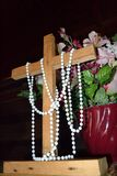 Easter Cross on the Alter. Plain wooden cross with flowers and decorated with a string of pearls on the alter for Easter Royalty Free Stock Photos
