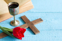 Easter cross bible and chalice tulip on blue Royalty Free Stock Images