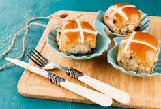 Easter cross-buns. Three tasty Easter cross-buns served on chopping board on blue wooden background stock photo