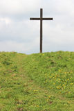 Easter Cross on green hill with path up to cross. View of a cross that is placed on the sea wall at Pilling in Lancashire each Easter with a pass leading up to Royalty Free Stock Photography