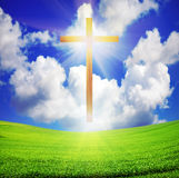 Easter cross over green field and blue sky Stock Image