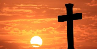 Easter cross at sunrise. With orange sky and clouds Stock Photos