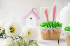 Easter cupcake decorated with bunny ears for dessert and flowers. Easter cupcake decorated with bunny ears and grass for dessert and flowers stock photos