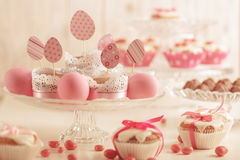 Easter cupcakes decorated with pink candy, paper eggs and ribbon Stock Image