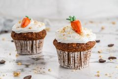 Easter cupcakes or muffins with cream and carrot candy on light marble background. Holiday cake celebration, delicious dessert,. Close up royalty free stock image