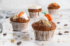 Easter cupcakes or muffins with cream and carrot candy on light marble background. Holiday cake celebration, delicious dessert,. Close up royalty free stock photography