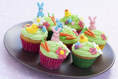 Easter cupcakes on plate. Easter cupcakes with bunny, eggs, flowers and carrots made from icing sugar Stock Images