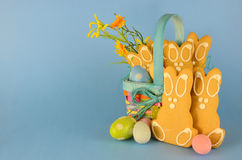 Easter. Cute gingerbread easter bunny cookies in a colorful basket with eggs and flowers on a blue background. Copy space stock images