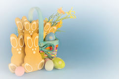 Easter. Cute gingerbread easter bunny cookies in a colorful basket with eggs and flowers on a blue background. White vignette and copy space royalty free stock image