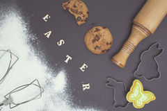 Easter day background. Flour, baked cookies and kitchen utensils on dark table. Wooden letters. Royalty Free Stock Photo
