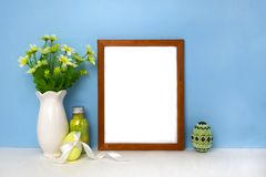 Easter decor with blank frame mockup on blue wall. Fnd white table. Home holiday interior background empty design eggs vase branches bouquet flowers april royalty free stock photo