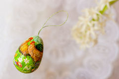 Easter decor colorful painted egg, natural flowers on white background of white lace doily. Festive decorations.With Royalty Free Stock Photography