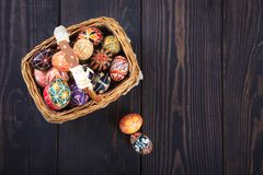 Easter decorated eggs in the basket, on a wooden background stock images