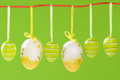 Easter decorated eggs hanging on red string  on green backgound. Royalty Free Stock Image