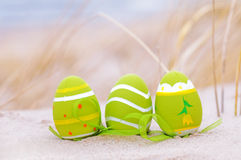 Easter decorated eggs on sand. Beach and ocean in the background stock image