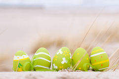 Easter decorated eggs on sand. Beach and ocean in the background royalty free stock photos