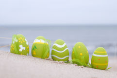 Easter decorated eggs on sand. Beach and ocean in the background stock photography