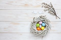 Easter decoration – nest with colorful decorative eggs, dove figurines and willow branches. Top view, close up, flat lay. On white wooden background stock photography