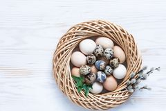 Easter decoration – nest, willow, natural eggs. Top view, close up, flat lay on white wooden background.  stock photo