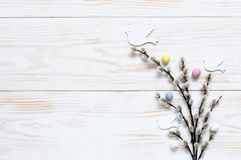 Easter decoration – pattern of colorful decorative eggs and dove figurines on willow branches. Top view, close up, flat. Lay on white wooden background royalty free stock photos
