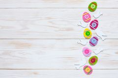 Easter decoration – pattern of colorful decorative eggs and dove figurines. Top view, close up, flat lay on white wooden. Background royalty free stock images