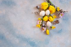Easter decoration – willow, tulips, narcissus, bunny figurines and natural eggs. Top view, close up, flat lay on light. Concrete background royalty free stock photos