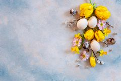 Easter decoration – willow, tulips, narcissus, bunny figurines and natural eggs. Top view, close up, flat lay on light. Concrete background royalty free stock photo