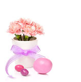 Easter Decoration. Easter eggs with pink carnations in a vase decorated with ribbon on white royalty free stock photography