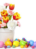 Easter Decoration. Spring flowers in a white pot with colorful easter eggs isolated on white royalty free stock photo