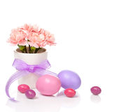 Easter Decoration. Pink Carnation flowers in a white pot with easter eggs on white royalty free stock photography