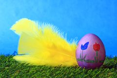Easter decoration. Consisting of colorfully painted Easter egg and a yellow feather on a blue background Royalty Free Stock Photo