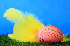Easter decoration. With red colored Easter egg with yellow feathers on artificial turf Royalty Free Stock Photography