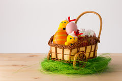 Easter Decoration. Eggs, carriage, little yellow chicks on wooden table with white background stock images