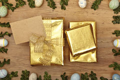 Easter decoration, blank card and  golden presents on wood Royalty Free Stock Photo