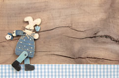 Easter decoration with a blue bunny on a wooden background in sh. Abby chic style with a blue checked frame for greeting card Stock Photos
