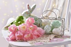 Easter decoration with bunch of pink tulips eggs and bunny. Easter decoration with bunch of pink tulips,eggs and bunny figurines in pastel colors royalty free stock images
