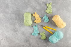 Easter decoration, bunny rabbits made of crochet colorful yarn. Ongrey texture background. Homemade decor. Top view. Spring Easter holydays concept royalty free stock image