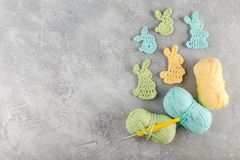 Easter decoration, bunny rabbits made of crochet colorful yarn. Ongrey texture background. Homemade decor. Top view. Spring Easter holydays concept royalty free stock photos