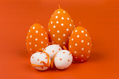 Easter decoration - candles with colored eggs on the orange background. Stock Image