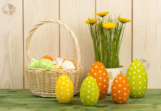 Easter decoration - candles, flower and basket with eggs. Royalty Free Stock Image