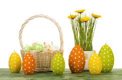 Easter decoration - candles, flower and basket with eggs on wooden background. Stock Photography