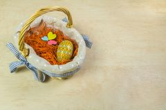 Easter decoration, colored wooden egg and colorful hearts in a basket on wooden background. Easter decoration, colored patterned wooden egg and colorful three stock photo