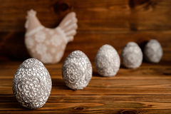 Easter decoration - decorative hen and eggs on wooden background. Stock Image
