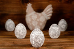 Easter decoration - decorative hen and eggs on wooden background. Stock Photos