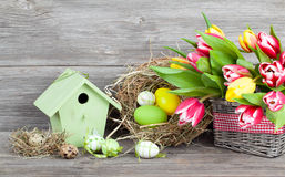 Easter decoration with eggs, birdhouse and tulips. wooden background stock photos