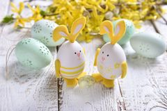 Easter decoration with eggs with bunny ears and forsythia. Easter decoration with eggs with bunny ears, mint eggs and forsythia flowers lying on white wooden royalty free stock photos