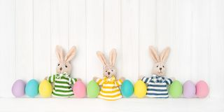 Easter decoration eggs funny bunnies wooden background Stock Image