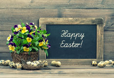 Easter decoration eggs, pansy flowers and vintage blackboard Royalty Free Stock Image
