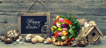 Easter decoration with eggs and tulip flowers. Retro style toned Stock Photos